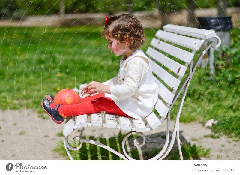 Liebenswertes kleines Mädchen spielt mit einem Ball, der auf einer Parkbank sitzt. Lifestyle Freude Glück schön Gesicht Sommer Kind Mensch Kleinkind Frau