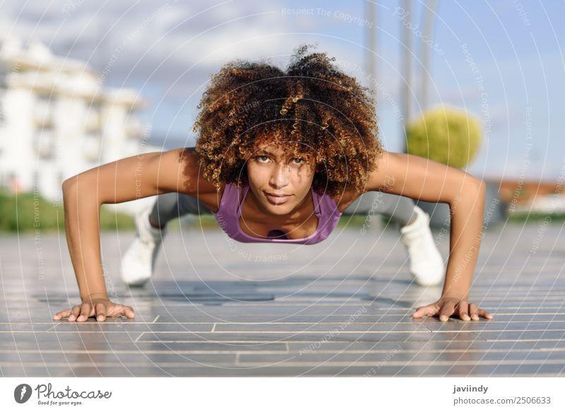 Schwarze Frau, die Liegestütze auf dem Stadtboden macht. Lifestyle Körper Haare & Frisuren Freizeit & Hobby Sport Arbeit & Erwerbstätigkeit Junge Frau