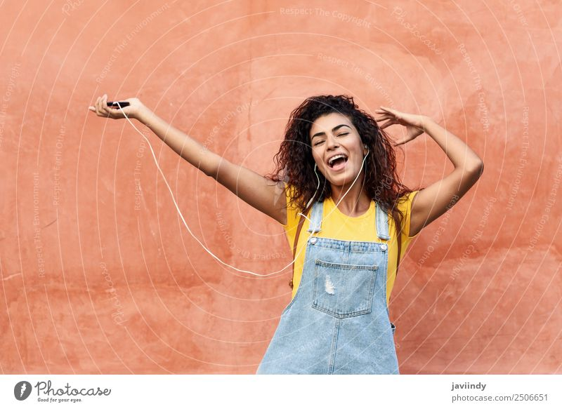 Glückliche Frau, die Musik hört und mit Kopfhörern tanzt. Lifestyle schön Haare & Frisuren Telefon Technik & Technologie Junge Frau Jugendliche Erwachsene 1