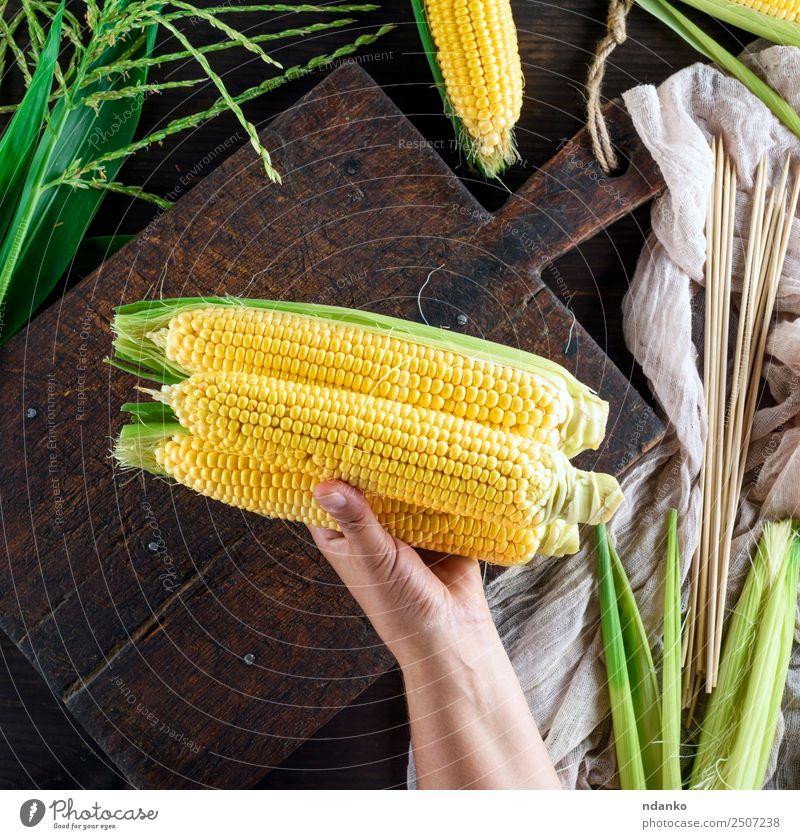 Hand hält drei reife gelbe Kolben. Gemüse Ernährung Vegetarische Ernährung Tisch Natur Pflanze Blatt Holz alt frisch natürlich oben braun gold grün Mais