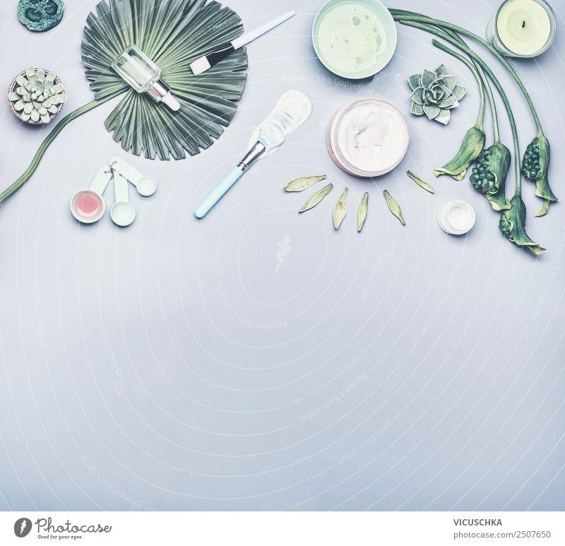 Hautpflegekosmetik und Gesichtsmaske. Verschiedene Kosmetikprodukte: Serum, Creme und Gel mit tropischen Blättern und Blüten auf grauem Hintergrund, Ansicht von oben . Modernes Schönheitskonzept