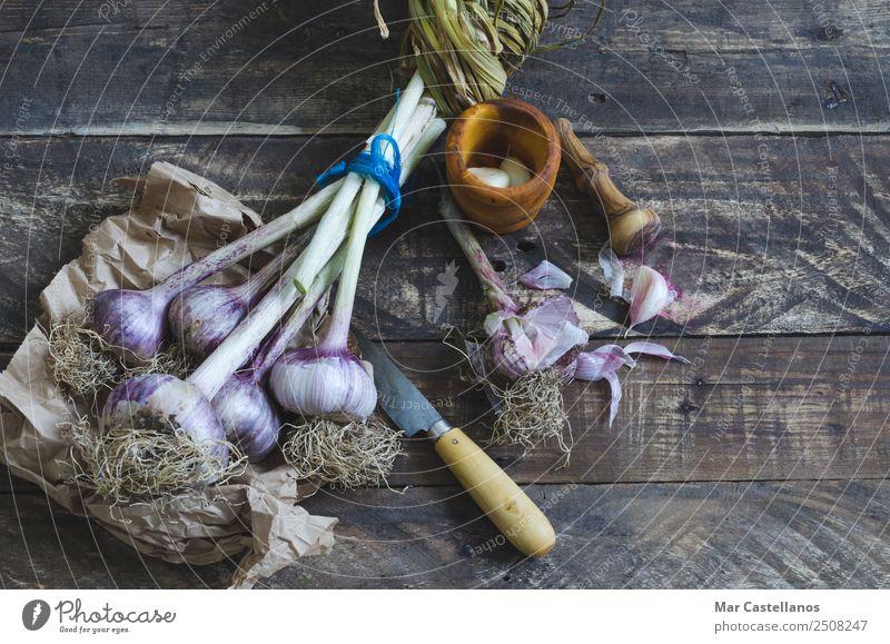 Knoblauchstrauß mit Geschirr auf Holzuntergrund Gemüse Kräuter & Gewürze Ernährung Essen Bioprodukte Messer Küche Natur Pflanze Sommer Nutzpflanze füttern