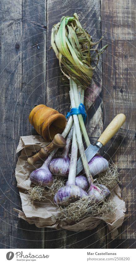 Knoblauchstrauß mit Geschirr auf Holzuntergrund Gemüse Kräuter & Gewürze Ernährung Essen Messer Küche Natur Pflanze Nutzpflanze füttern frisch natürlich braun