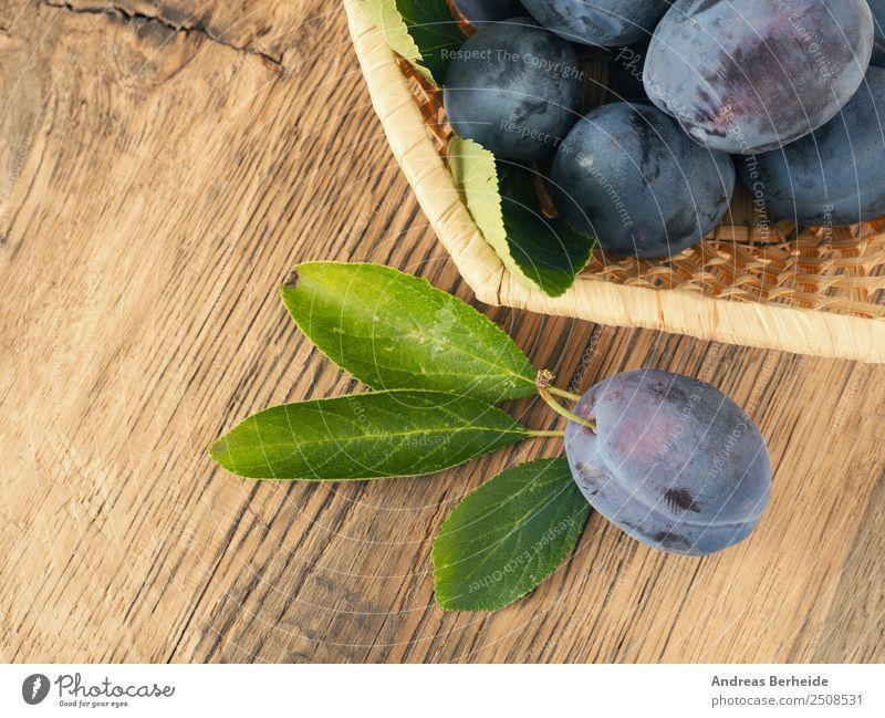 Frisch geerntete Bio Pflaumen in einem Korb auf Holztisch Natur Sommer Gesunde Ernährung Lebensmittel Frucht süß lecker Ernte Bioprodukte Dessert
