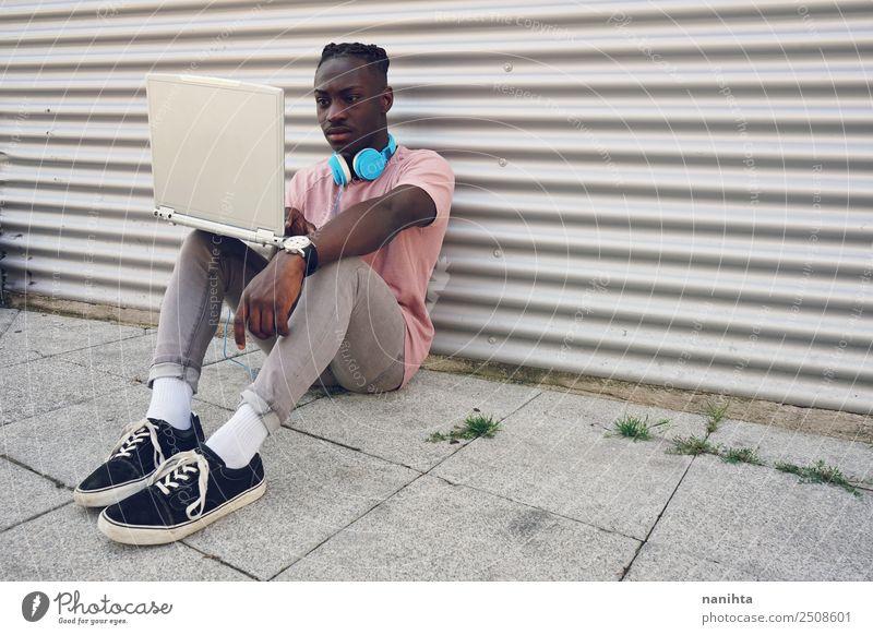 Junger schwarzer Teenager mit seinem Laptop Lifestyle Stil Freizeit & Hobby Student Headset Computer Notebook Kopfhörer Technik & Technologie