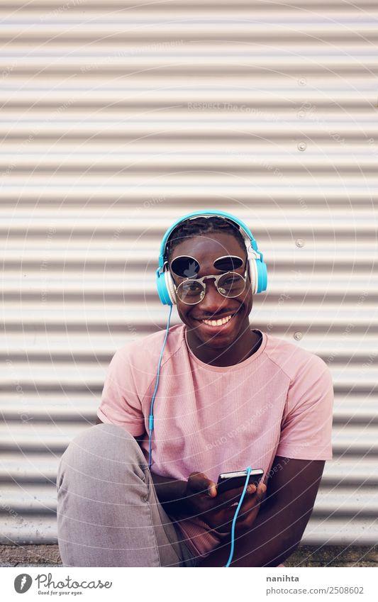 Junger schwarzer Mann, der Musik hört. Lifestyle Stil Freizeit & Hobby Handy Headset Kopfhörer Technik & Technologie Unterhaltungselektronik Mensch maskulin