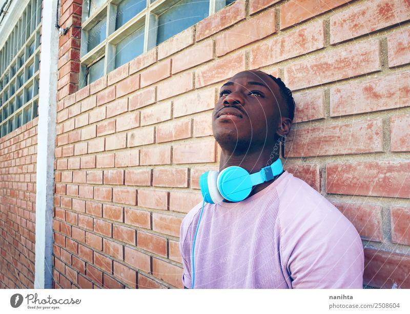 Junger schwarzer Mann gegen eine Ziegelmauer Lifestyle Stil Design Sinnesorgane Erholung Freizeit & Hobby Headset Kopfhörer Technik & Technologie