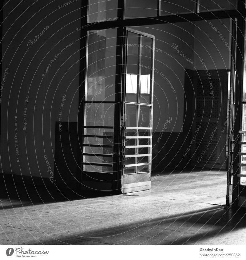 Der Schatten ehemaligen Andrangs. Haus Industrieanlage Bahnhof Gebäude Architektur Halle Tür Glas Metall bedrohlich dreckig dunkel kalt Stimmung Schwarzweißfoto