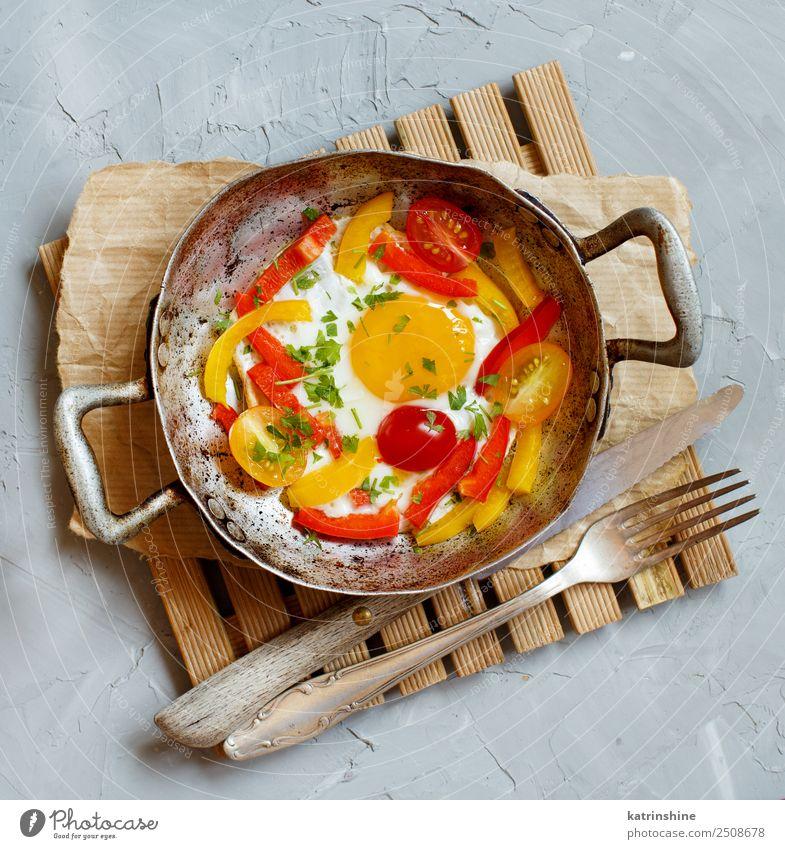 Spiegelei mit Paprika und Tomaten Gemüse Frühstück Pfanne Gabel Tisch frisch hell gelb grau rot Cholesterin kochen & garen Ei fette Nahrung Lebensmittel braten