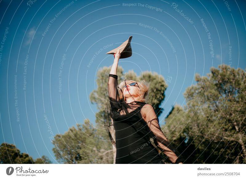Glückliche blonde Frau, die bei Sonnenuntergang im Wald den Arm mit einem Hut in der Hand hebt. Lifestyle Stil Freude Erholung Ferien & Urlaub & Reisen Ausflug