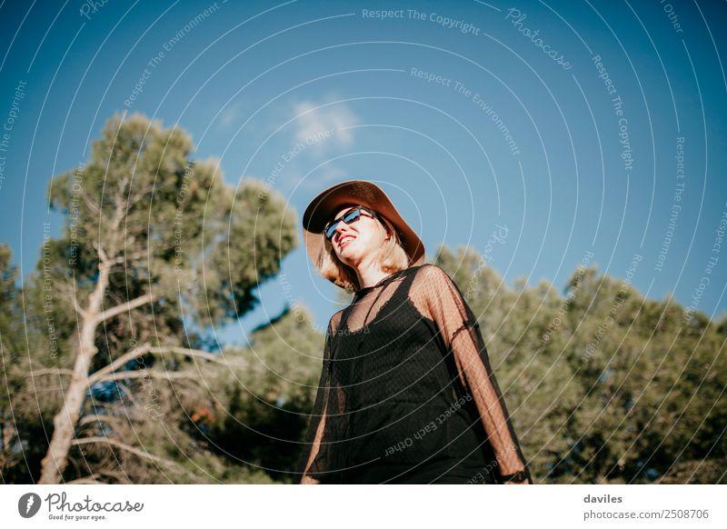Niederwinkelporträt eines süßen blonden Mädchens beim Sonnenbad in der Natur mit Kiefernwald im Hintergrund. Lifestyle elegant Stil Freude Wellness Leben