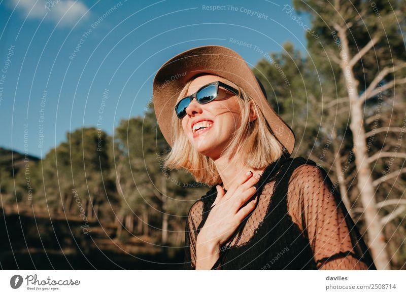 Glückliche blonde Frau mit Sonnenbrille und Hut, die die Sonne in der Natur genießt Lifestyle elegant Stil Freude schön Erholung Ferien & Urlaub & Reisen