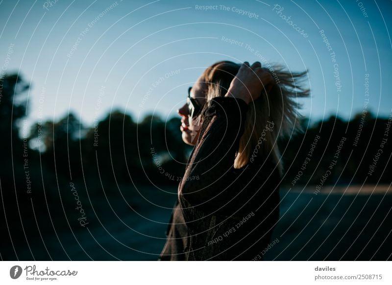 Blondes Mädchen mit Sonnenbrille posiert bei Sonnenuntergang mit einer Hand im Haar Lifestyle elegant Stil schön Mensch feminin Junge Frau Jugendliche 1