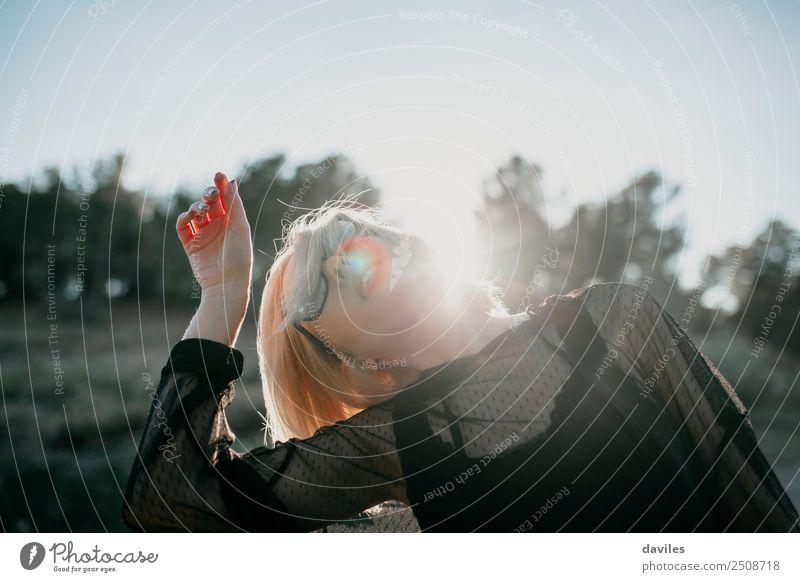 Kühle blonde Frau, die bei Sonnenuntergang tanzt und die Hand nahe an ihren Kopf hebt Lifestyle elegant Stil Freude schön stimmig feminin Junge Frau Jugendliche