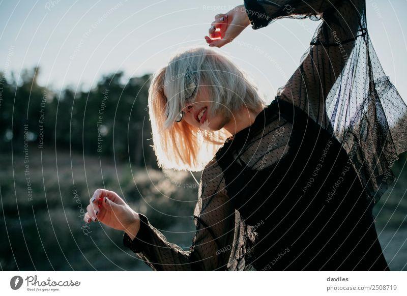 Blonde Frau in schwarzem Kleid führt bei Sonnenuntergang einen Tanz auf. Lifestyle elegant Stil Freude schön Mensch feminin Junge Frau Jugendliche Erwachsene