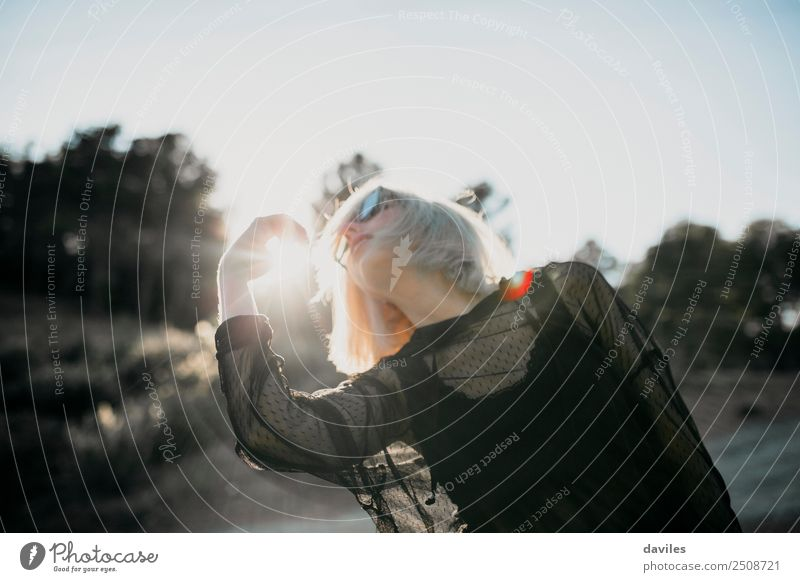 Kühle blonde Frau in schwarzem Kleid, die bei Sonnenuntergang einen Tanz vorführt, mit der Sonne im Hintergrund. Lifestyle elegant Stil Freude stimmig Mensch