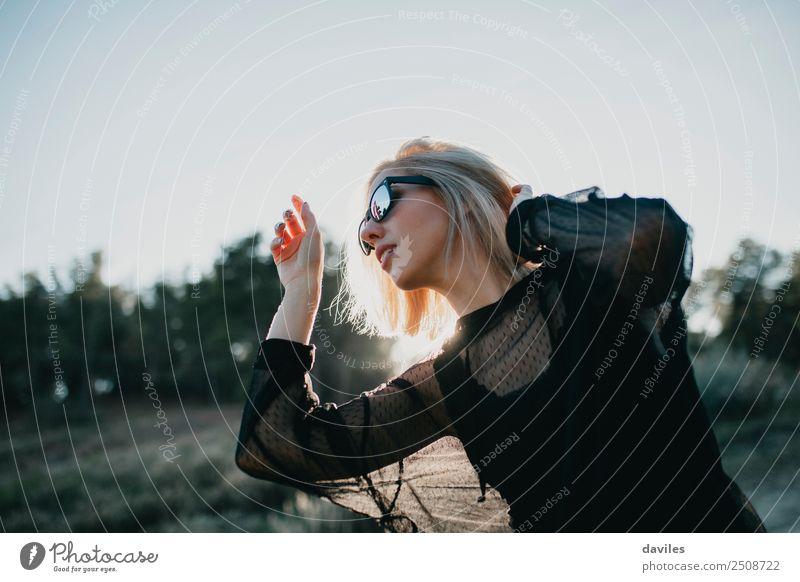 Blonde Frau mit schwarzem Kleid und Sonnenbrille führt im Gegenlicht Tanz in der Natur auf Lifestyle elegant Stil Freude schön Wellness Leben stimmig Wohlgefühl