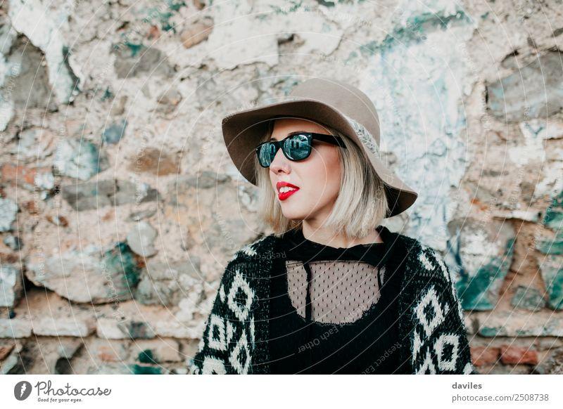 Bildnis eines blonden Mädchens mit Hut und Sonnenbrille, das mit einer Steinmauer im Hintergrund wegschaut. Lifestyle kaufen Reichtum elegant Stil Freude schön