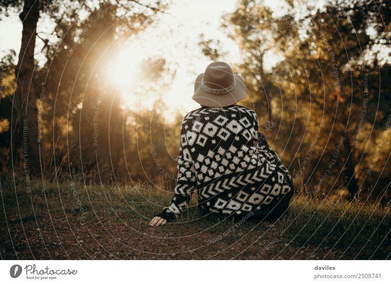 Frau mit Hut auf dem Rücken, die bei Sonnenuntergang im Wald in die Sonne schaut Lifestyle Wellness Wohlgefühl Erholung Ferien & Urlaub & Reisen Abenteuer