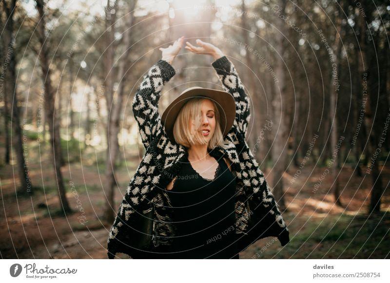Cooles blondes Mädchen mit Hut und schwarzer Kleidung tanzt mitten im Wald Lifestyle Freude Wellness Freizeit & Hobby Ferien & Urlaub & Reisen Freiheit Mensch