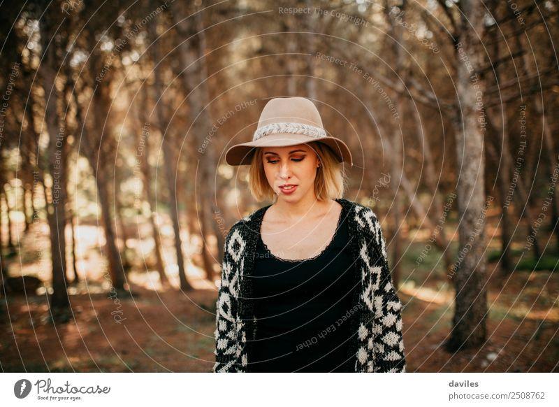 Porträt einer jungen Frau mit Hut, die bei Sonnenuntergang im Wald spazieren geht Lifestyle Freizeit & Hobby Ferien & Urlaub & Reisen Abenteuer Freiheit