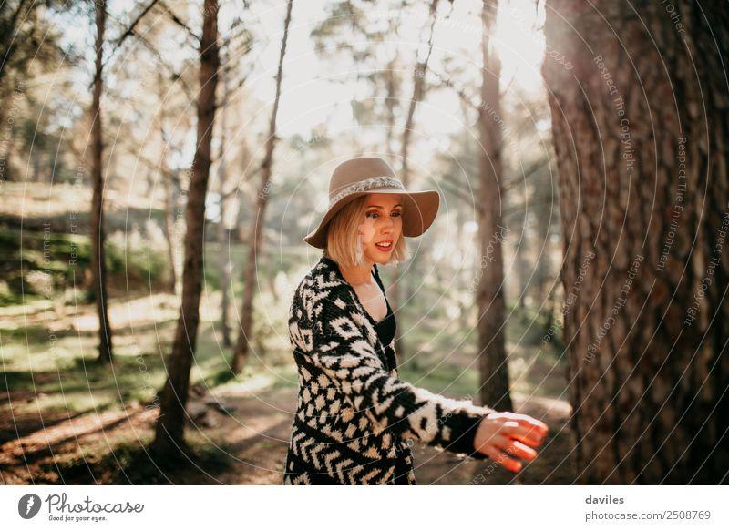 Frau, die bei Sonnenuntergang im Wald spazieren geht und mit der Hand einen Baumstamm erreicht. Lifestyle Freude Freizeit & Hobby Mensch feminin Junge Frau