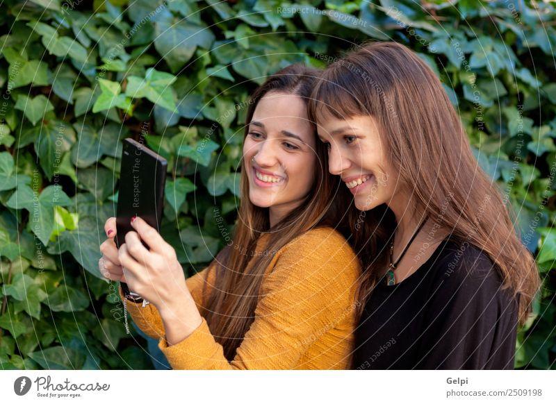 Nette Schwestern mit blauen Augen Lifestyle Freude Glück schön Leben Spielen Telefon Handy PDA Technik & Technologie Internet Frau Erwachsene Freundschaft