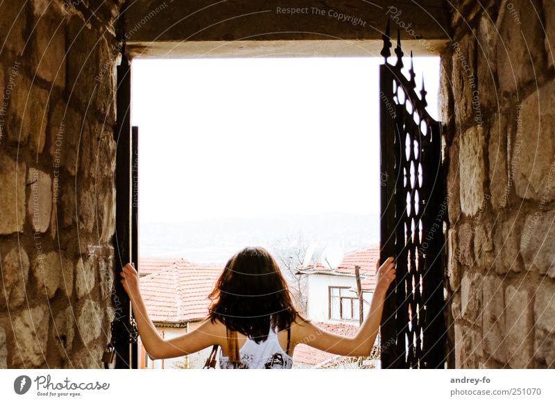 Andere Welt. Junge Frau Jugendliche Erwachsene 1 Mensch 18-30 Jahre Mauer Wand Tür T-Shirt brünett Stein entdecken Blick neu Neugier Abenteuer festhalten