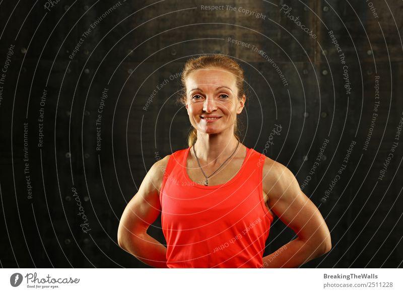 Close up vorderen Oberkörper Porträt eines mittleren Alters sportliche Frau in Sportkleidung in der Turnhalle über dunklen Hintergrund, Blick auf die Kamera und lächelnd