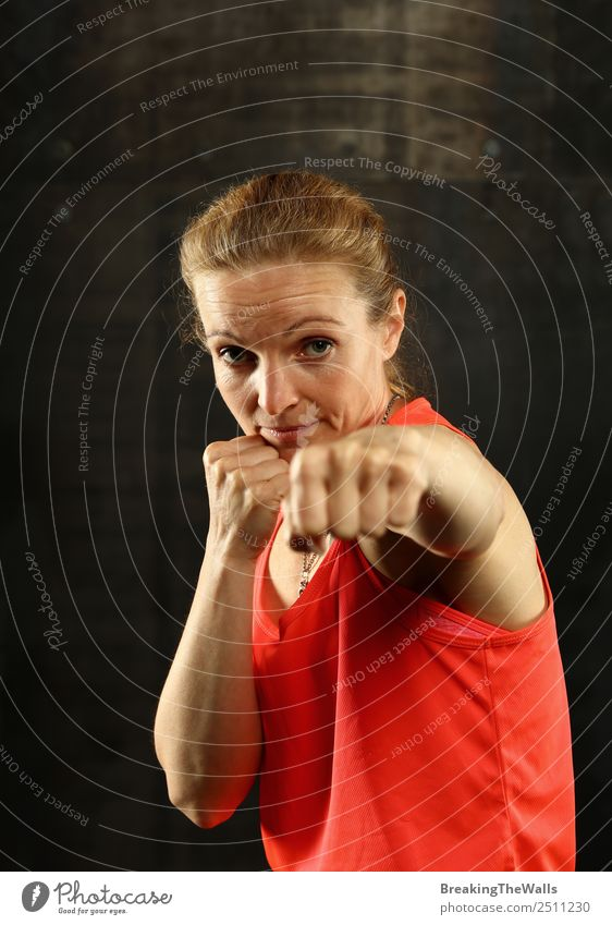 Nahaufnahme von vorne Porträt eines jungen Mitte Erwachsene sportliche Frau in Sportkleidung in der Turnhalle über dunklen Hintergrund, stehend in Boxhaltung mit Händen und Fäusten, Blick auf die Kamera