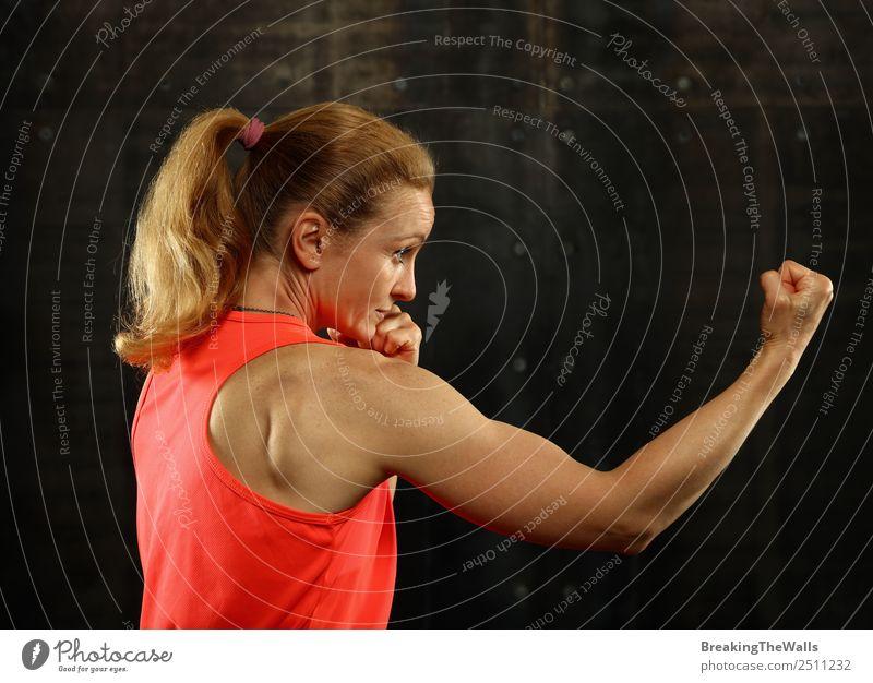 Close up Seitenansicht Profil Porträt eines jungen mittleren Alters sportliche Frau Schattenboxen in Sportkleidung in der Turnhalle über dunklen Hintergrund, Blick weg