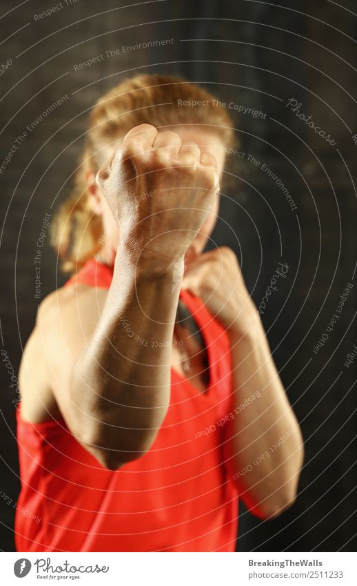 Nahaufnahme Frontalporträt einer jungen sportlichen Frau mittleren Alters in Sportkleidung im Fitnessstudio vor dunklem Hintergrund, stehend in Boxhaltung mit Händen und Fäusten, in die Kamera blickend
