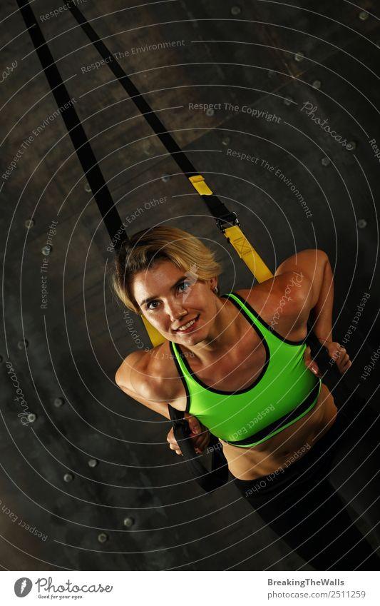 Eine junge sportliche Frau beim Crossfit-Training, die mit Trx-Suspension-Fitnessbändern vor dunklem Hintergrund trainiert, Vorderansicht, Blick in die Kamera