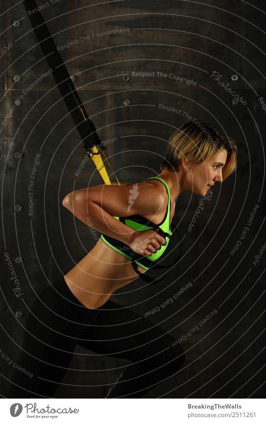 Seitenprofilansicht Porträt einer jungen sportlichen Frau beim Crossfit-Training, die mit Trx-Suspension-Fitnessbändern vor dunklem Hintergrund trainiert und wegschaut