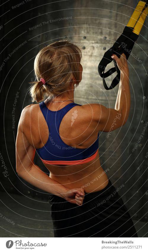 Rückansicht Porträt eines jungen mittleren Alters sportliche Frau beim Crossfit-Training, üben mit trx Aussetzung Fitness-Bänder über dunklen Hintergrund