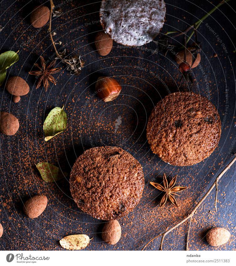 gebackene Muffins auf einem schwarzen Tisch Kuchen Dessert Süßwaren Frühstück Holz Essen frisch klein oben braun Pulver Hintergrund Bäckerei Schokolade