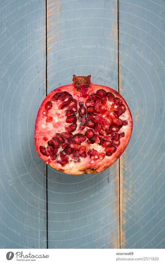 Granatapfel auf blauem Holzgrund Frucht rot Lebensmittel Gesunde Ernährung Foodfotografie Vegetarische Ernährung Diät organisch roh frisch exotisch