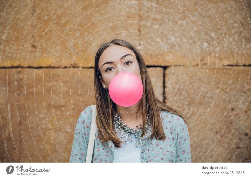 Junges Mädchen bläst Kaugummi über einen Steinmauerhintergrund Lifestyle Freude Glück schön Gesicht Mensch Frau Erwachsene Jugendliche Mund Lippen Mode brünett