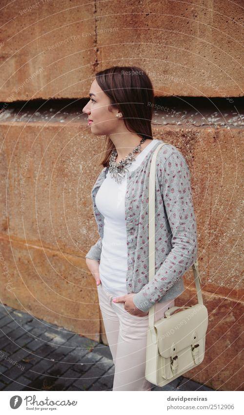 Junge trendige Frau über Steinmauer Hintergrund Lifestyle elegant Stil schön Mensch Erwachsene Herbst Straße Mode Bekleidung Jeanshose Jacke brünett stehen