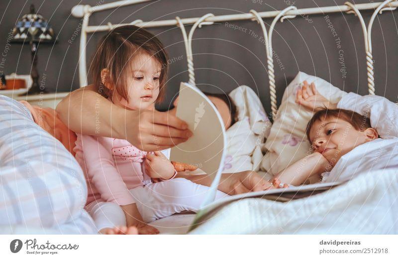 Baby Mädchen beim Lesen Buch mit Familie im Bett Lifestyle Freude Glück schön Erholung Freizeit & Hobby lesen Schlafzimmer Kind Junge Frau Erwachsene Eltern