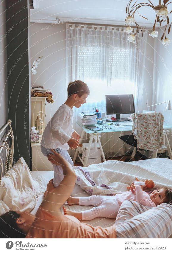 Junge, der mit seiner Familie über das Bett springt. Lifestyle Freude Glück schön Erholung Freizeit & Hobby Spielen Schlafzimmer Kind Baby Frau Erwachsene