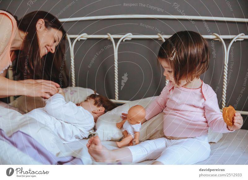 Kleines Mädchen mit Puppe und Keks, das über dem Bett sitzt. Essen Frühstück Lifestyle Freude Glück Erholung Freizeit & Hobby Schlafzimmer Kind Baby Junge Frau