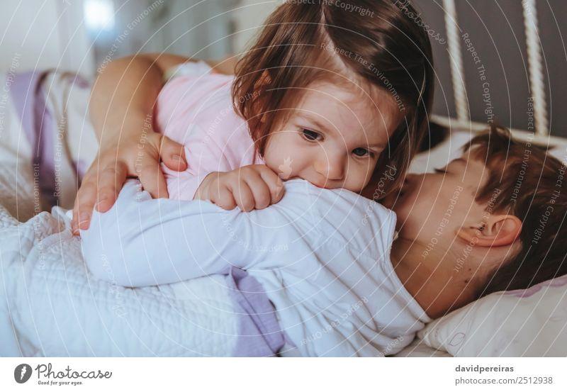 Kleines Mädchen spielt über dem Jungen, der im Bett liegt. Lifestyle Freude Glück Erholung Freizeit & Hobby Spielen Schlafzimmer Kind Baby Frau Erwachsene