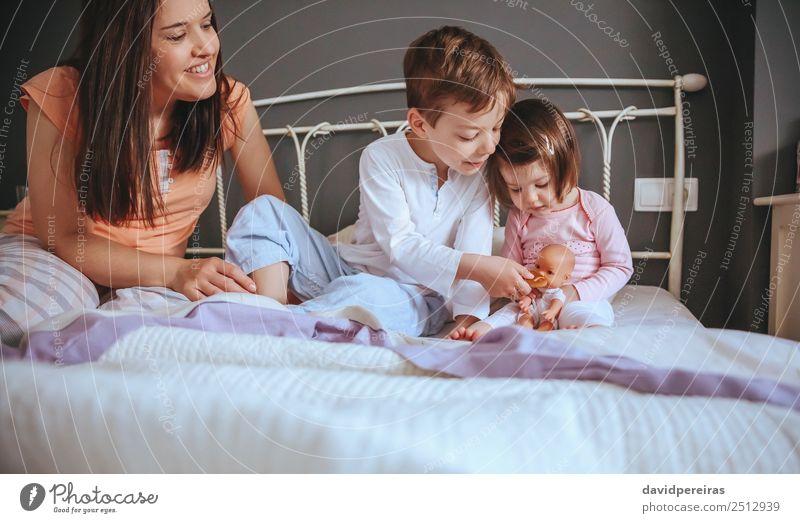 Kinder füttern Puppe mit Keksen über dem Bett sitzend Essen Frühstück Lifestyle Freude Glück schön Erholung Freizeit & Hobby Schlafzimmer Baby Junge Frau