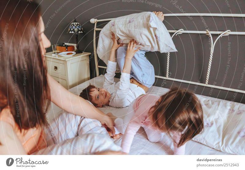 Entspannte Mutter und Söhne spielen über dem Bett. Lifestyle Freude Glück schön Erholung Freizeit & Hobby Spielen Schlafzimmer Kind Baby Junge Frau Erwachsene