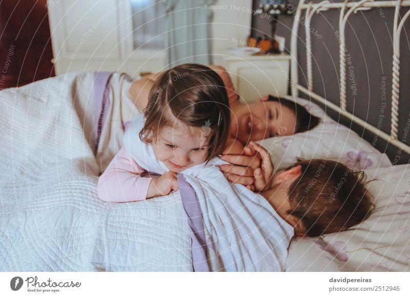 Kleines Mädchen spielt über dem Jungen, der im Bett liegt. Lifestyle Freude Glück schön Erholung Freizeit & Hobby Spielen Schlafzimmer Kind Baby Frau Erwachsene