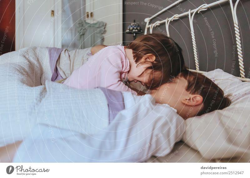 Kleines Mädchen spielt mit dem Jungen über dem Bett. Lifestyle Freude Glück schön Erholung Freizeit & Hobby Spielen Schlafzimmer Kind Baby Frau Erwachsene