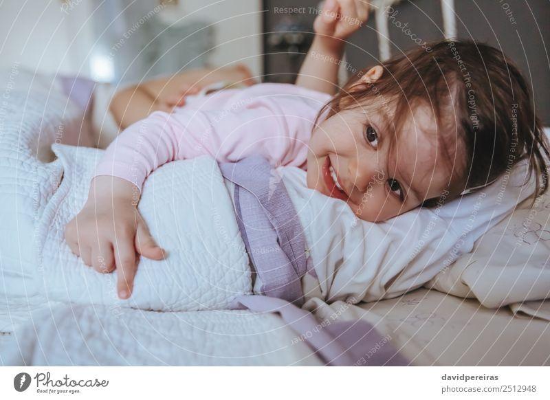 Kleines Mädchen lächelnd über dem Bett liegend Lifestyle Freude Glück Erholung Freizeit & Hobby Spielen Schlafzimmer Kind Mensch Baby Frau Erwachsene Eltern