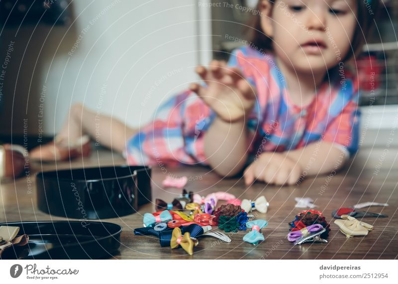 Baby Mädchen spielt mit Haarspangen, die auf dem Boden liegen. Lifestyle Freude Glück schön Spielen Haus Kind Mensch Frau Erwachsene Kindheit Hand Bekleidung