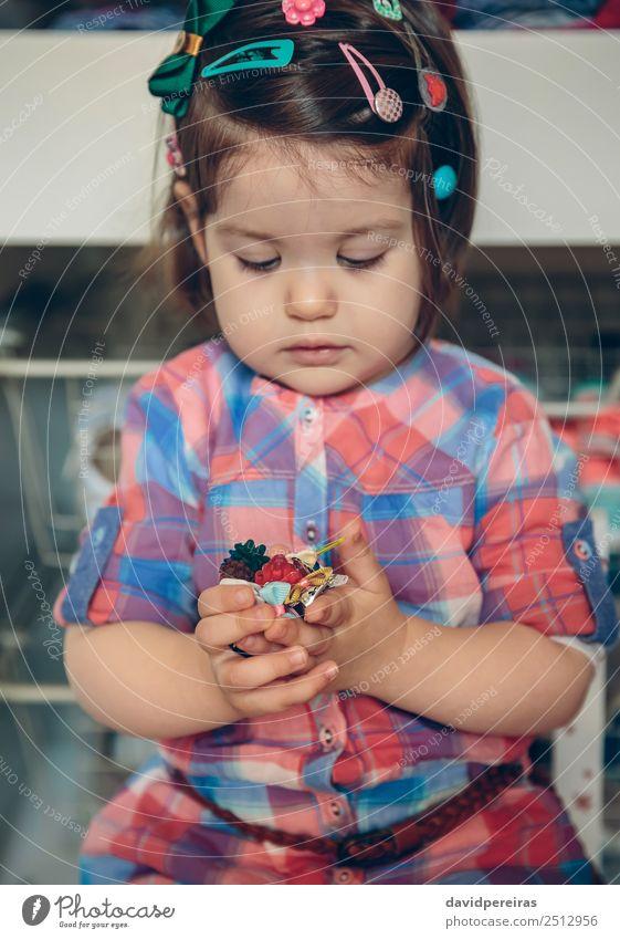 Babymädchen spielt mit Haarspangen in den Händen Lifestyle Freude Glück schön Spielen Haus Kind Mensch Kleinkind Frau Erwachsene Kindheit Hand Blume Mode